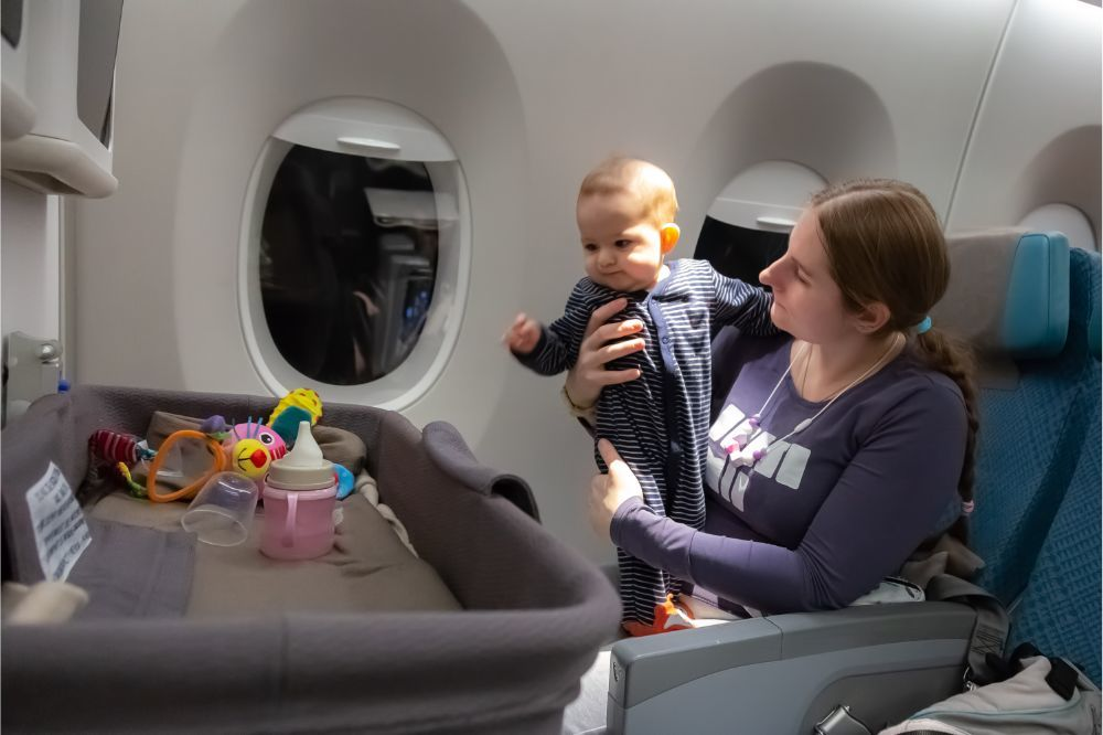 Infant plays on mother hands at the airplane with baby bassinet during the flight