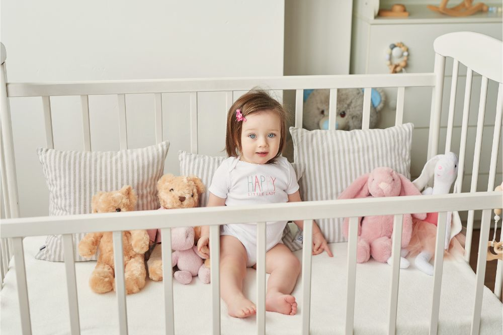 girl in a crib with toys in the children's room